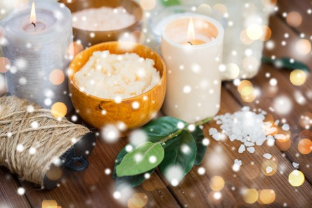 natural therapy: beauty, spa, therapy and natural cosmetics concept - body scrub, salt and candles on wood over lights and snow Stock Photo