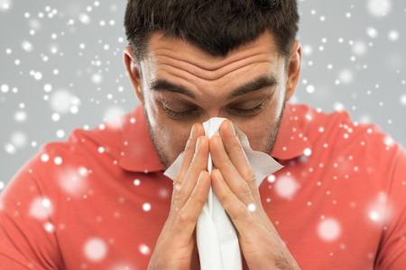 people, healthcare, rhinitis, winter and cold concept - sick man with paper wipe blowing nose over snow on gray background Stock Photo