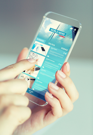 web screen: business, technology, internet and people concept - close up of woman hand holding and showing transparent smartphone with news web pages on screen Stock Photo