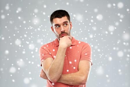 desconfianza: duda, la expresión, invierno, Navidad y concepto de la gente - hombre serio que piensa sobre la nieve sobre fondo gris