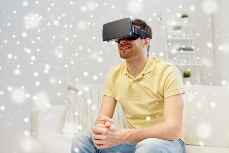 technology, gaming, augmented reality, entertainment and people concept - happy young man with virtual headset or 3d glasses playing video game over snow