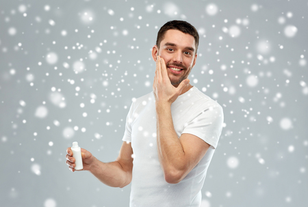 groomed: beauty, skin care, winter, christmas and people concept - smiling young man applying cream or lotion to face over snow on gray background Stock Photo