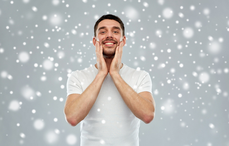 beauty, skin care, grooming, winter and people concept - happy young man touching his face applying aftershave over snow on gray background Stock Photo