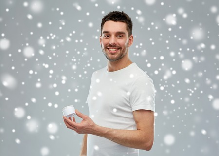 metrosexual: beauty, skin care, winter, christmas and people concept - smiling young man with cream jar over snow on gray background Stock Photo