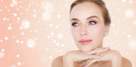 beauty woman: beauty, people, winter and bodycare concept - close up of beautiful young woman face and hands over beige background and snow Stock Photo