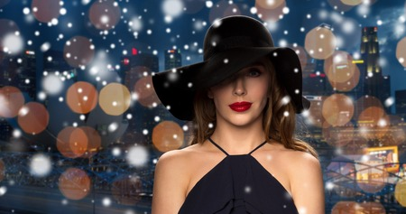 femme fatale: people, christmas, holidays, luxury and fashion concept - beautiful woman in black hat over night singapore city lights background and snow Stock Photo