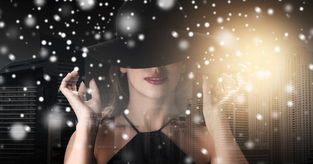 femme fatale: people, christmas, holidays and fashion concept - beautiful woman in black hat over dark over dubai city background with snow, double exposure and highlight