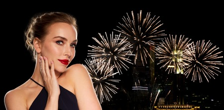 femme fatale: people, luxury, holidays, new year and fashion concept - beautiful woman in black with red lips over night city firework lights background Stock Photo