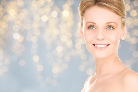 la beauté, les gens, les vacances et le concept de soins de la peau - belle jeune femme de toucher son visage au-dessus des lumières de fond