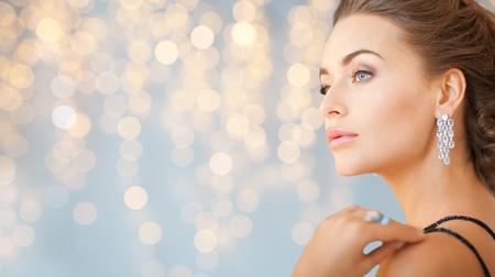 人、休日、宝石や高級コンセプト - ダイヤモンドの光の背景の上のイヤリングとイブニング ドレスで女性のクローズ アップ 写真素材