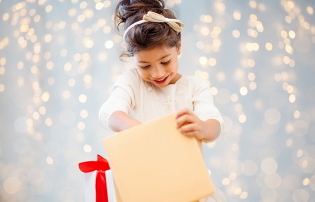 holidays, christmas, childhood and people concept - smiling little girl with gift box over lights background Stock Photo