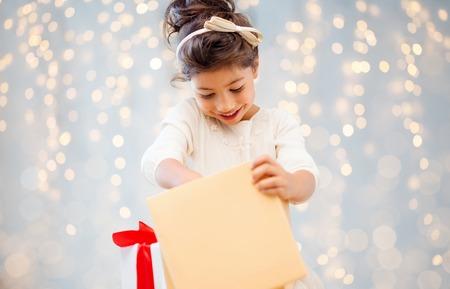 Urlaub, Weihnachten, Kindheit und Menschen Konzept - lächelnde kleine Mädchen mit Geschenk-Box über Lichter Hintergrund
