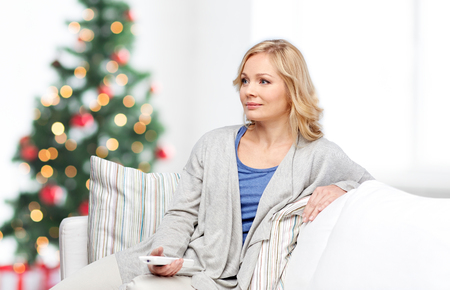 changing channel: television, holidays, leisure and people concept - smiling woman sitting on couch with tv remote control at home over christmas tree lights background