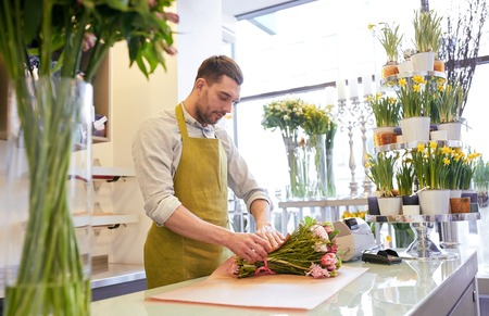 floristry: people, shopping, sale, floristry and consumerism concept - florist man wrapping flowers in paper at flower shop Stock Photo