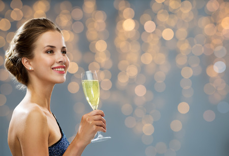 celebrities: party, drinks, holidays, luxury and celebration concept - smiling woman in evening dress with glass of champagne over black background Stock Photo