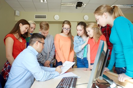 school exam: education, school, learning, teaching and people concept - group of students and teacher with tests in classroom