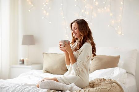 아침, 레저, 크리스마스, 겨울 및 사람들이 개념 - 행복 한 젊은 여자와 커피 또는 차 한잔 침대에서 집 침실
