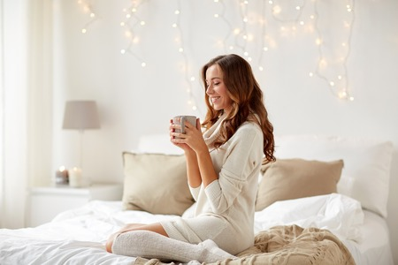 cosy: morning, leisure, christmas, winter and people concept - happy young woman with cup of coffee or tea in bed at home bedroom