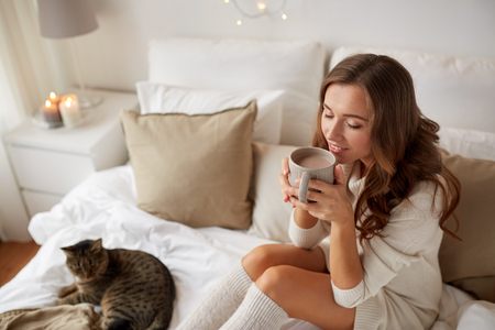 christmas tea: morning, leisure, christmas, winter and people concept - happy young woman with cup of coffee or tea in bed at home bedroom