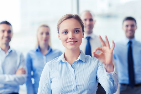 young entrepreneurs: business, people, gesture and teamwork concept - smiling businesswoman showing ok sign with group of businesspeople in office