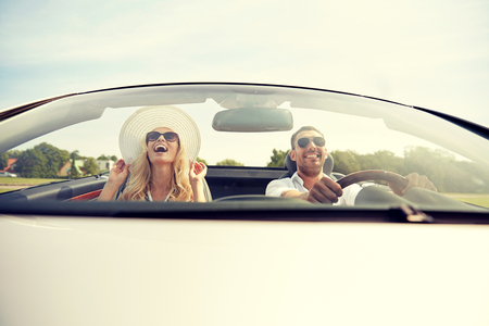 couple dating: road trip, travel, dating, couple and people concept - happy man and woman driving in cabriolet car outdoors