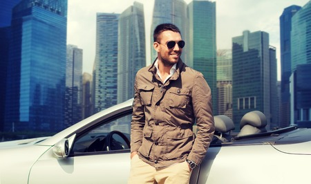 trip over: travel, tourism, road trip, transport and people concept - happy man near cabriolet car over city skyscrapers background