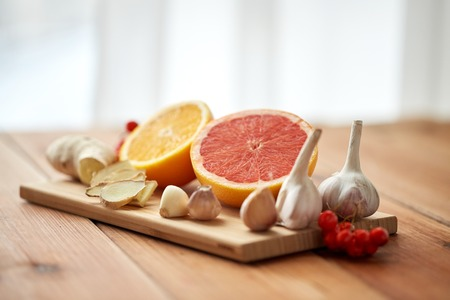 indigenous medicine: traditional medicine, cooking and ethnoscience concept - orange, grapefruit with ginger and garlic on wooden board