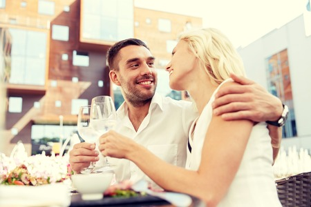 agua potable: love, dating, people and holidays concept - happy couple drinking wine or water at open-air restaurant and clinking glasses Foto de archivo