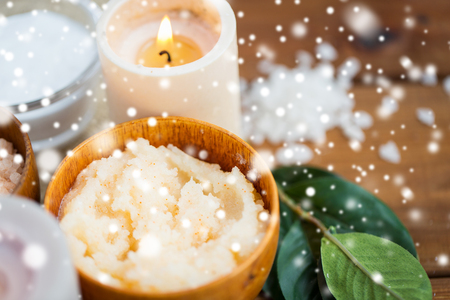 natural therapy: beauty, spa, therapy, natural cosmetics and wellness concept - close up of body scrub and candle on wood over snow