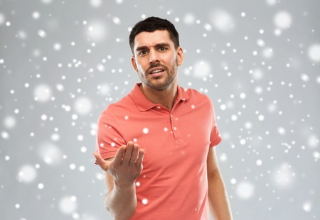 insulting: emotion, gesture, winter, christmas and people concept - arguing angry man proving something over snow on gray background