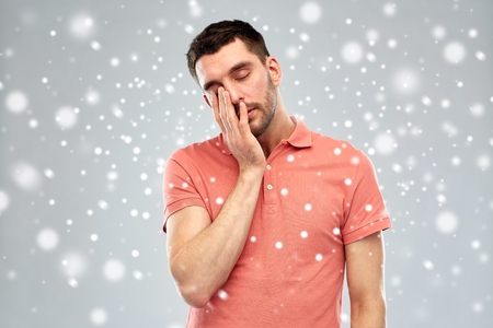 tiredness, stress, winter, christmas and people concept - tired sleepy young man over snow on gray background Stock Photo