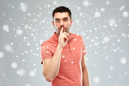 shush: silence, gesture, winter, christmas and people concept - serious young man making hush sign over snow on gray background