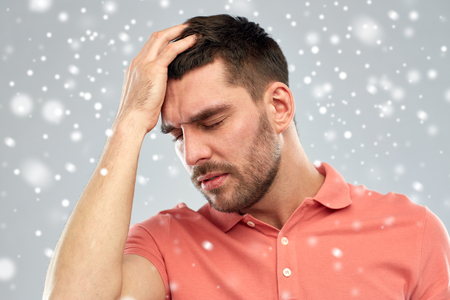 unhappy people: people, crisis, winter, christmas and stress concept - unhappy man suffering from head ache over snow on gray background