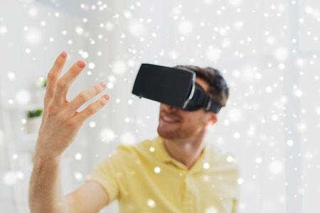 mediated: technology, augmented reality, gaming, entertainment and people concept - close up of young man with virtual headset or 3d glasses playing videogame at home over snow Stock Photo