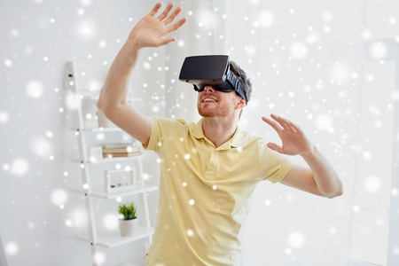 game over: technology, augmented reality, gaming, entertainment and people concept - happy young man with virtual headset or 3d glasses playing video game over snow