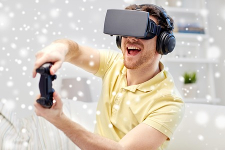 mediated: technology, augmented reality, gaming, entertainment and people concept - young man in headphones with virtual headset or 3d glasses with controller gamepad playing racing video game at home over snow Stock Photo