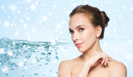 beauty skin: skin care, people, moisturizing and beauty concept - beautiful young woman face over water splash bubbles on blue background and snow