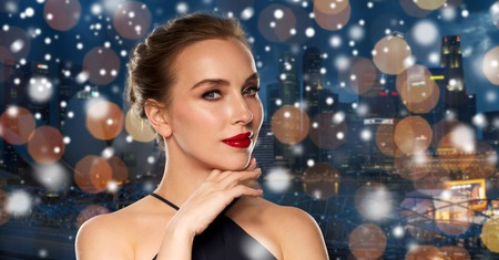 femme fatale: people, christmas, holidays, luxury and fashion concept - beautiful woman in black with red lips over night singapore city lights background and snow