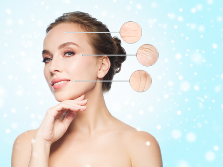 aging woman: beauty, people, aging, winter and skin concept - beautiful young woman touching her face over blue background and snow