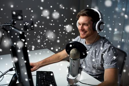 Technologie, gaming, entertainment, laten we spelen en mensen concept - gelukkig jonge man in headset met de computer van playing game thuis en streaming playthrough of walkthrough video over sneeuw Stockfoto - 65736276