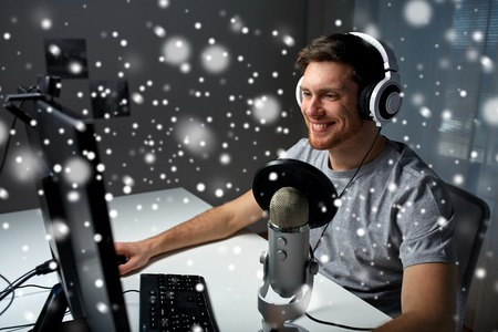 technology, gaming, entertainment, let's play and people concept - happy young man in headset with pc computer playing game at home and streaming playthrough or walkthrough video over snow Stock Photo - 65736276