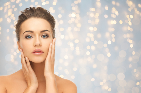 skin care woman: beauty, people, holidays and skin care concept - beautiful young woman touching her face over lights background