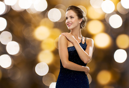 celebrities: people, holidays, jewelry and luxury concept - smiling woman in evening dress and pearl earring over lights background