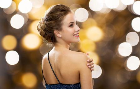las personas, las vacaciones, la joyería y el concepto de lujo - mujer sonriente en traje de noche y la pendiente de la perla sobre fondo de las luces