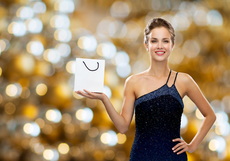 holydays: luxury, advertisement, holydays, people and sale concept - smiling woman with white blank shopping bag over lights background Stock Photo