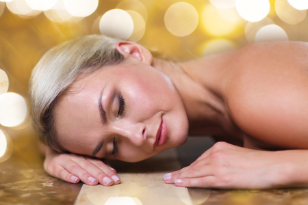 turkish bath: people, beauty, spa, healthy lifestyle and relaxation concept - beautiful young woman lying on hammam table in turkish bath over holidays lights background Stock Photo
