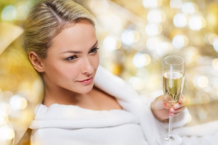 bath robe: people, and relaxation concept - beautiful young woman in white bath robe lying on chaise-longue and drinking champagne at spa over holidays lights background