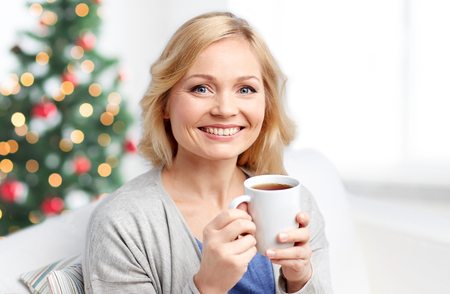 beautiful middle aged woman: people, holidays, cosiness, drinks and leisure concept - smiling woman with cup of tea or coffee at home over christmas tree background