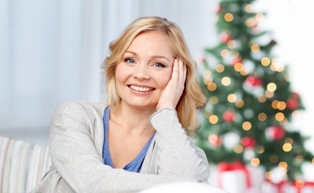 cosiness: holidays, people, cosiness and leisure concept - happy middle aged woman at home over christmas tree background Stock Photo