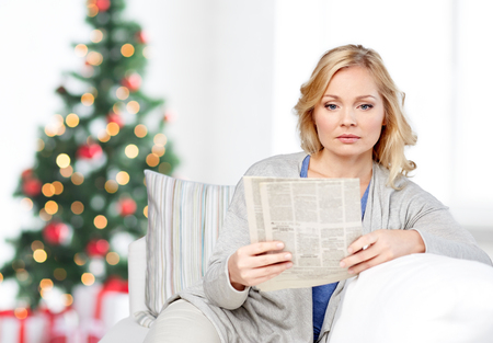 press media: news, press, media, holidays and people concept - woman reading newspaper at home over christmas tree background